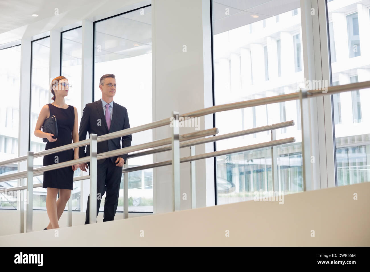 Business people walking by railing in office - Stock Image