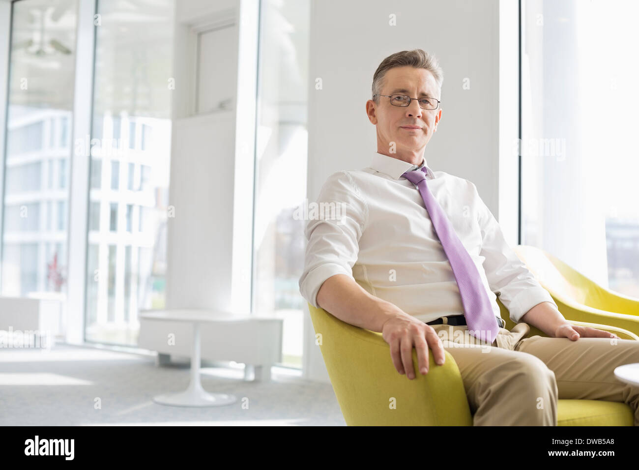 Portrait of confident businessman sitting at office lobby - Stock Image