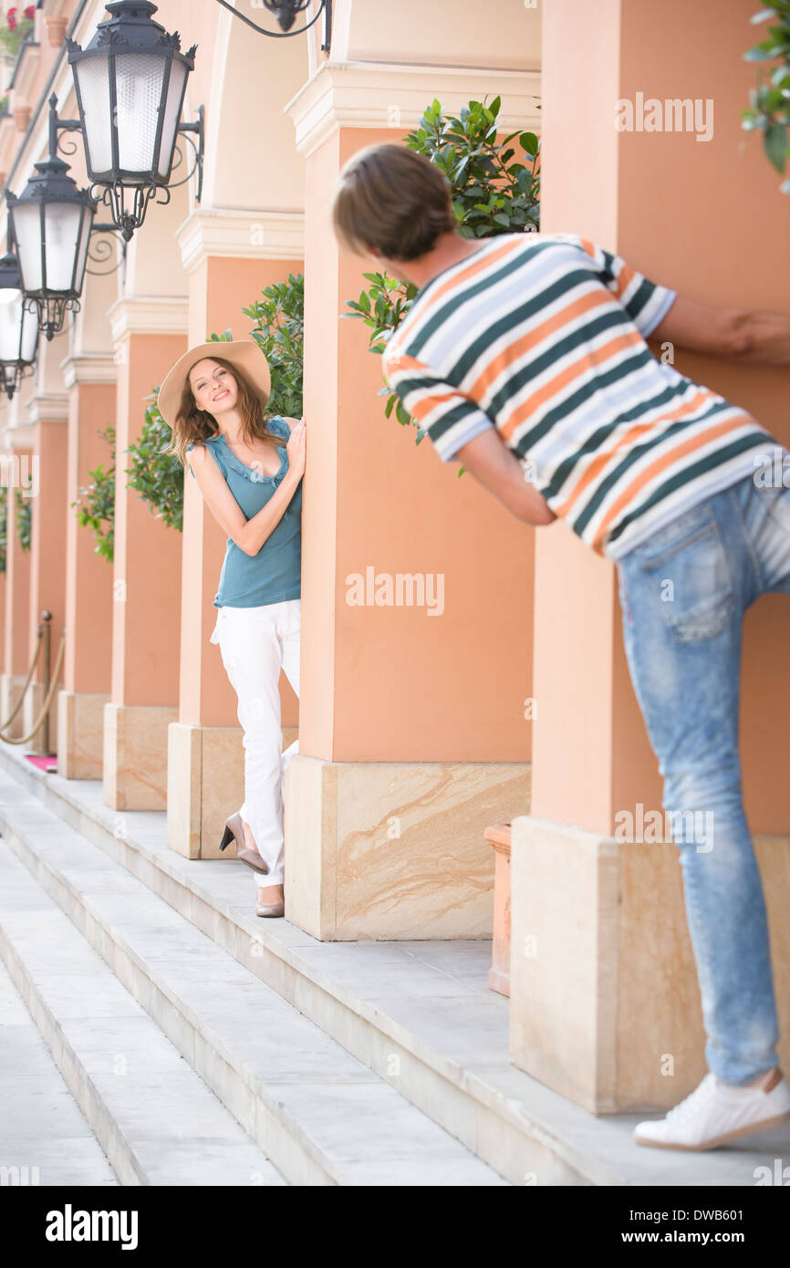Tourist couple playing hide-and-seek amongst columns - Stock Image