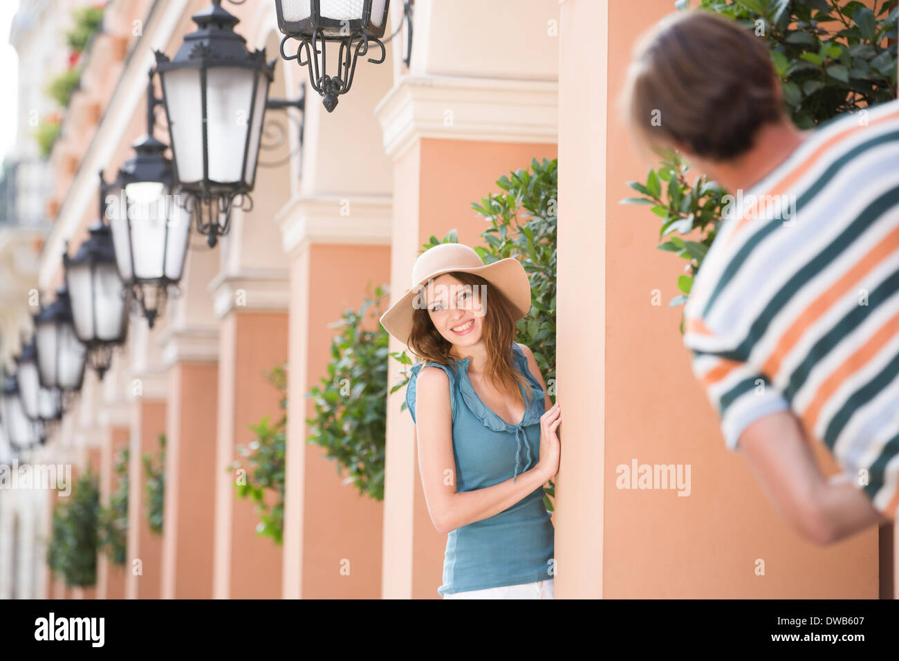 Happy woman playing hide-and-seek with man amongst pillars - Stock Image