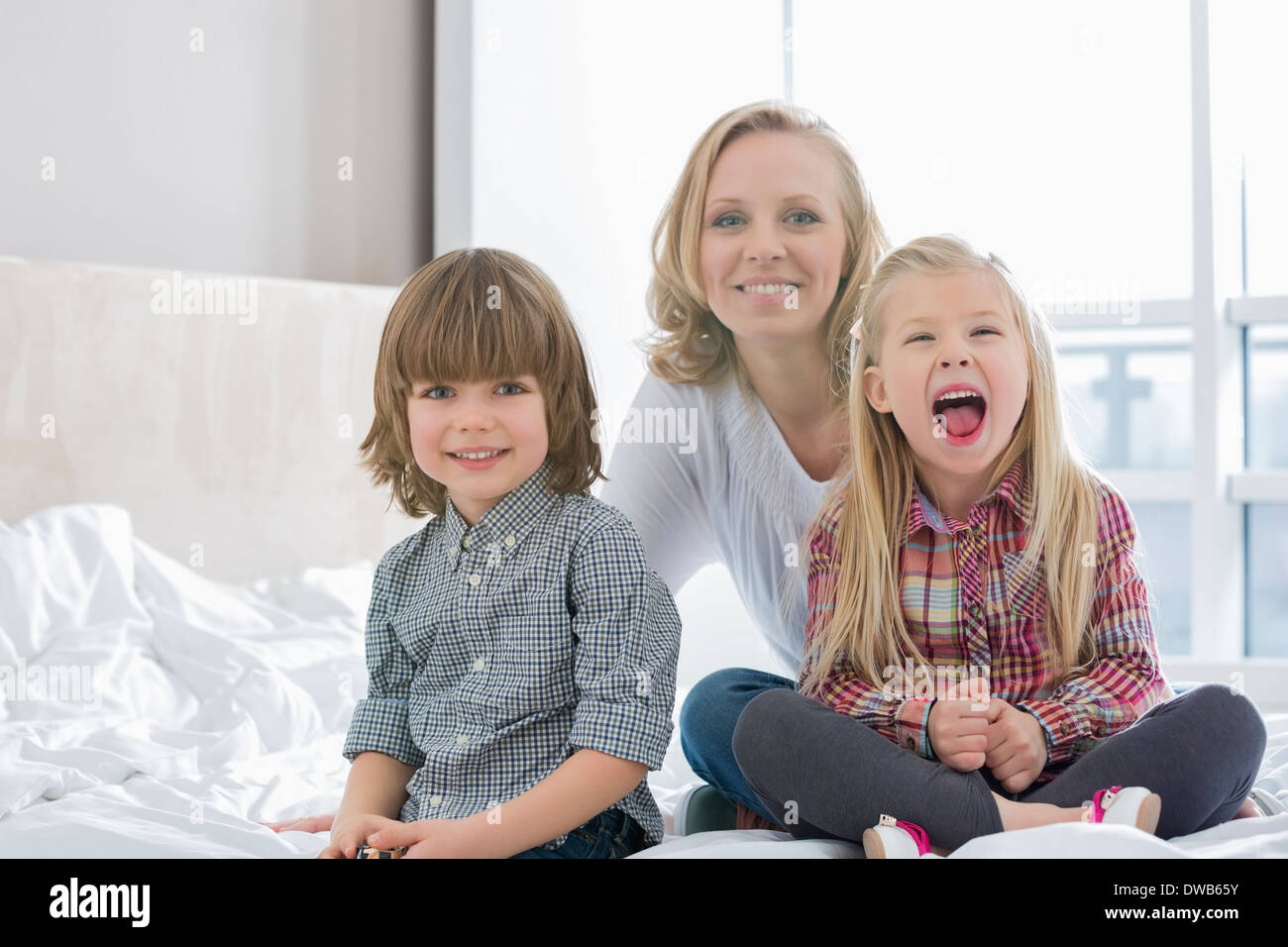 Portrait of happy mother with children in bedroom Stock Photo