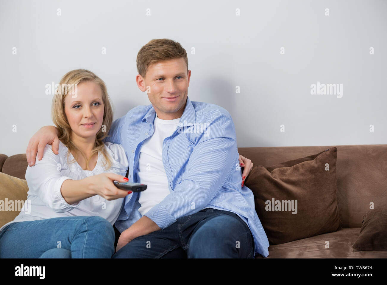 Mid adult couple watching television on sofa - Stock Image