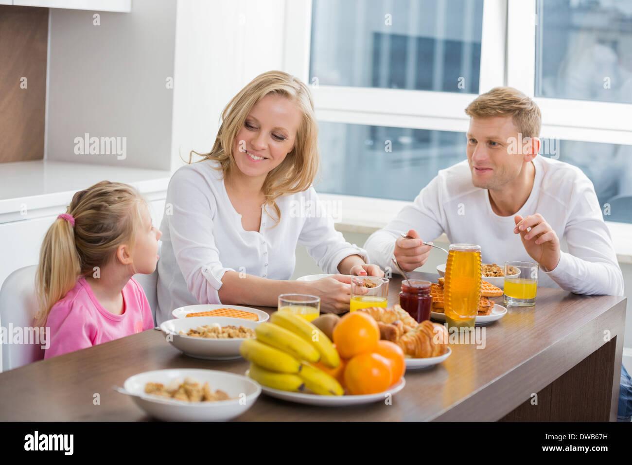 Happy family of three having breakfast at table Stock Photo