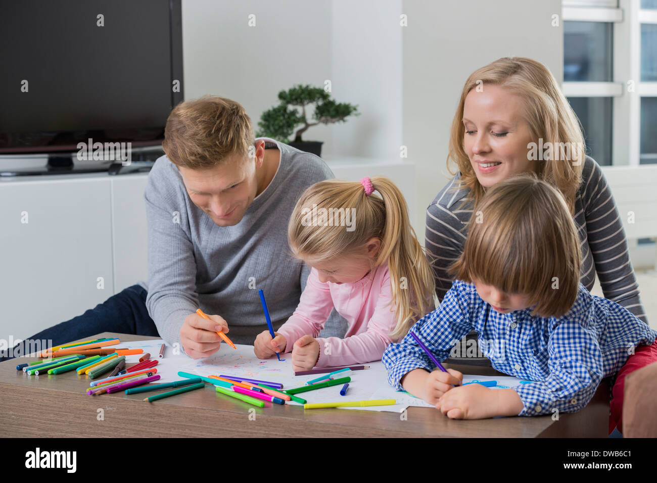 Parents with children drawing together at home - Stock Image