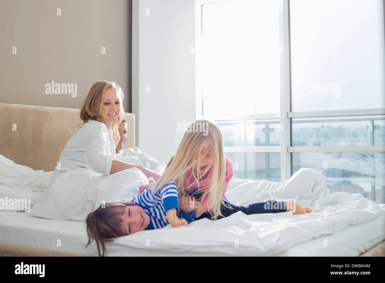 Happy parents looking at playful children in bedroom - Stock Image