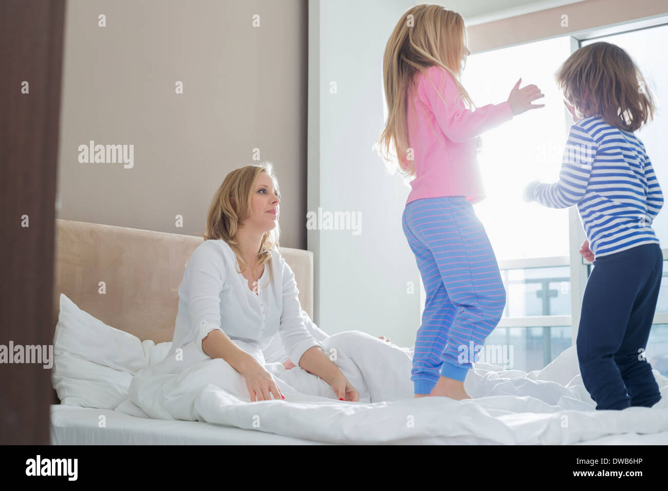 Mid adult parents looking at playful children in bedroom - Stock Image