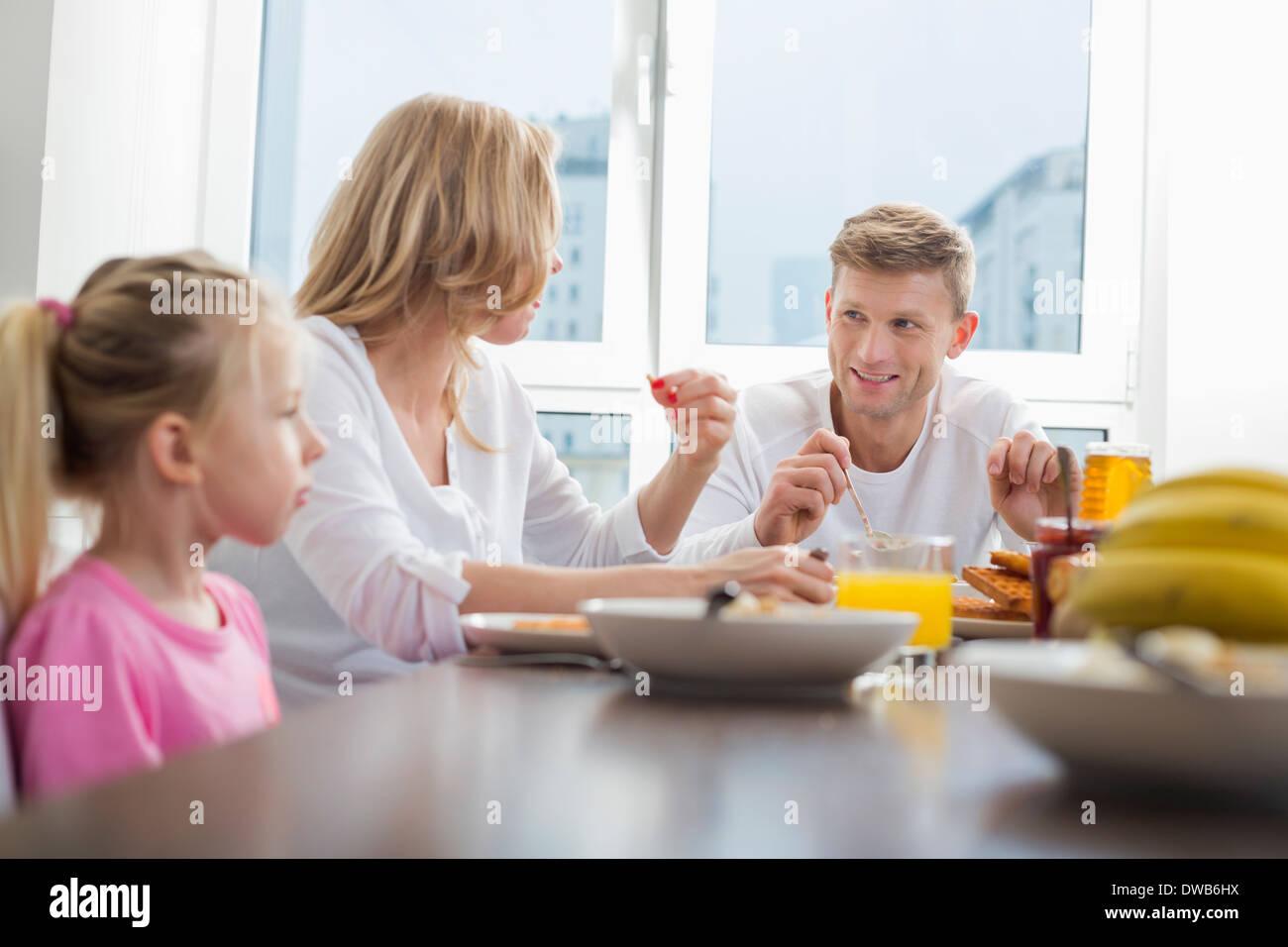 Happy family of three having breakfast at table - Stock Image