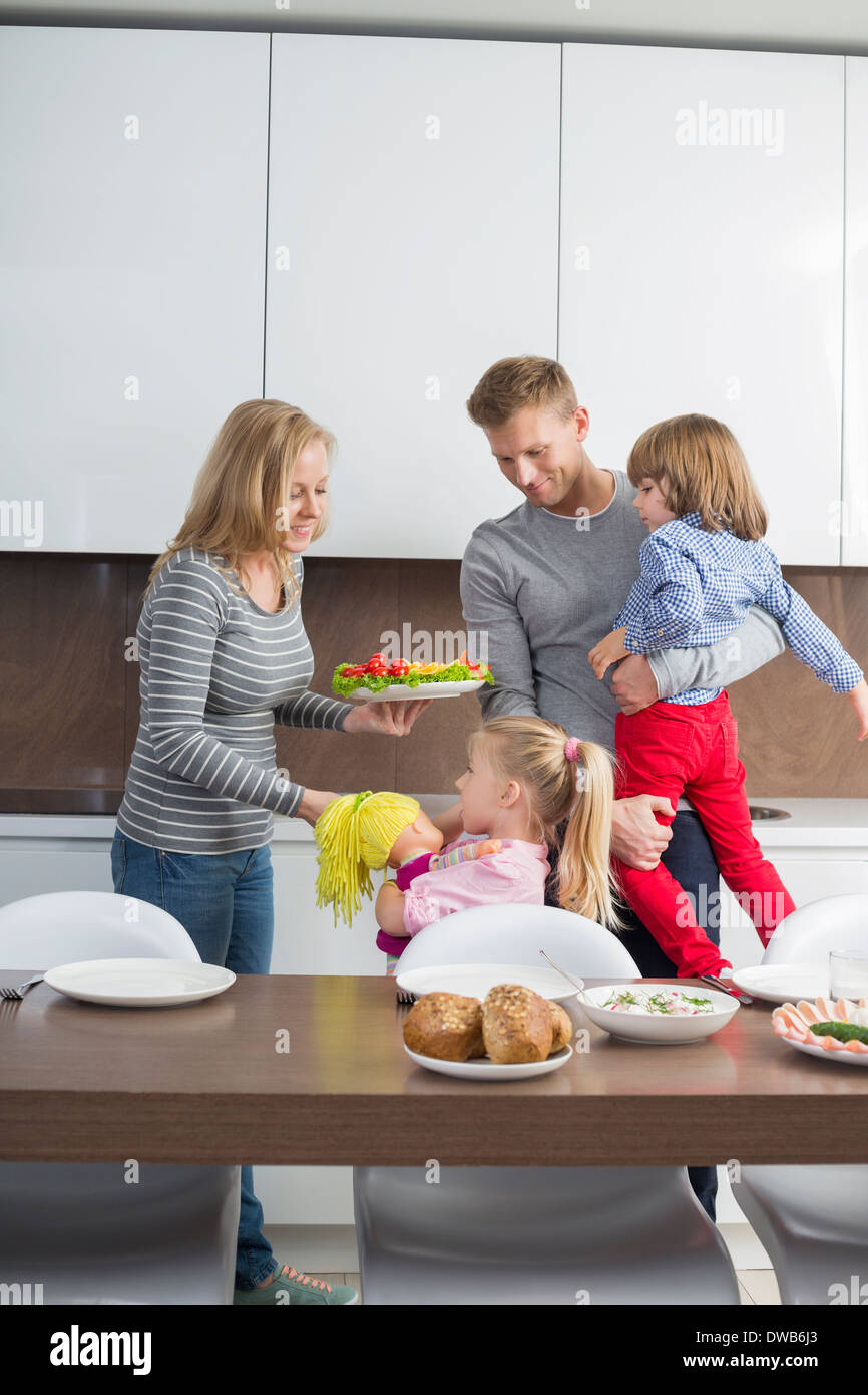 Happy family with children having meal in domestic kitchen - Stock Image