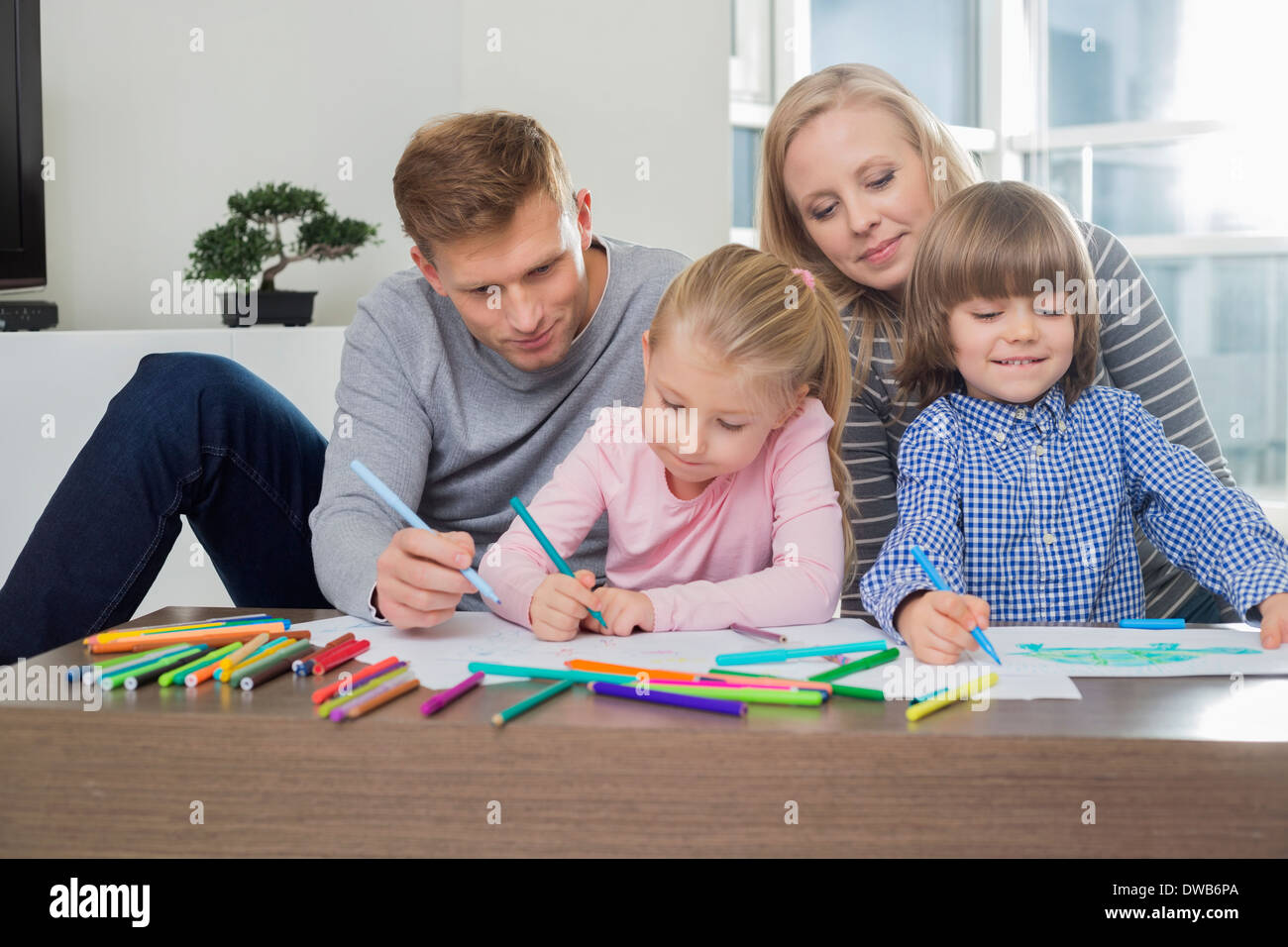 Mid adult parents with children drawing together at home - Stock Image