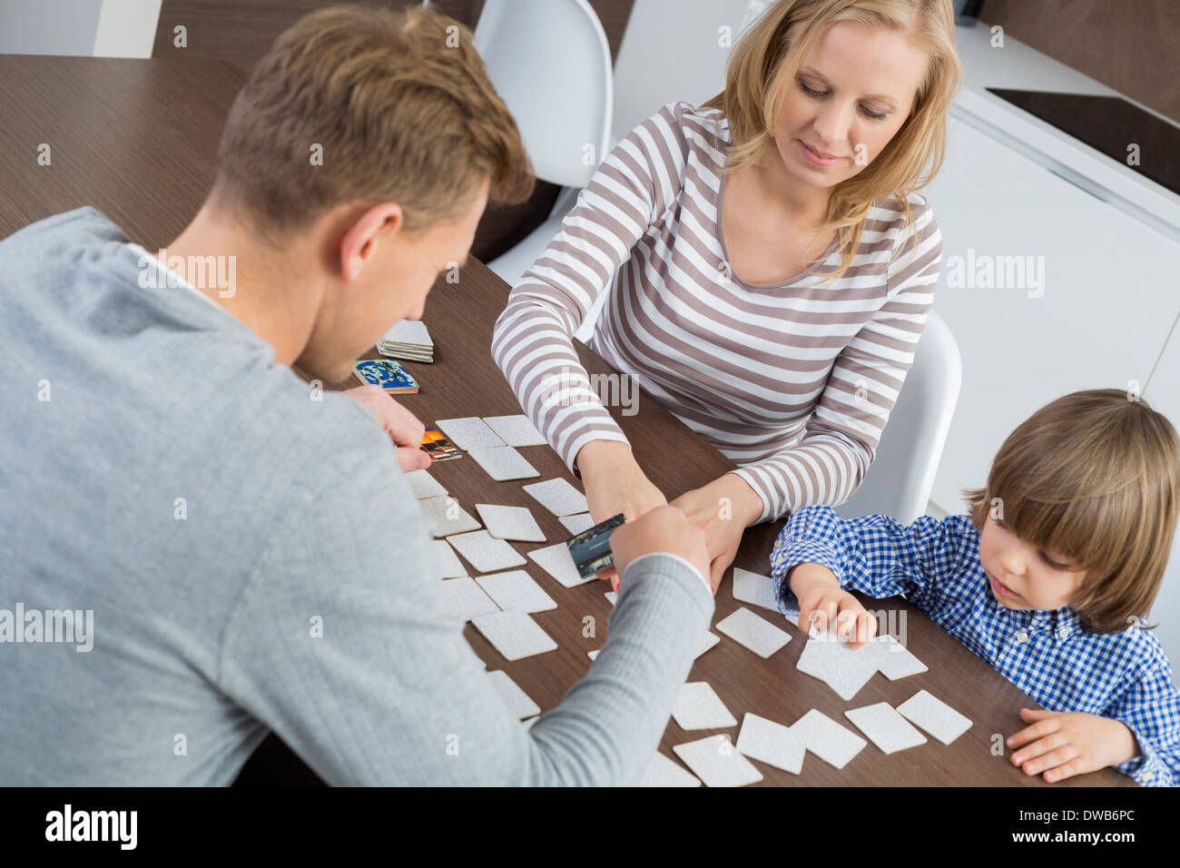 Family of three playing cards at home - Stock Image