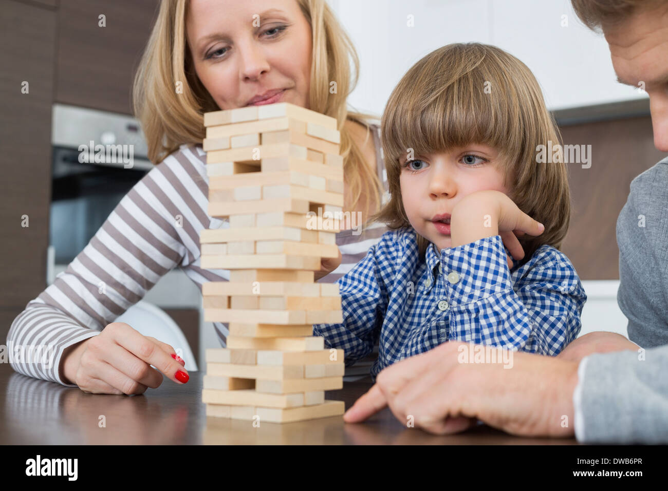 Family playing with wooden blocks at home - Stock Image