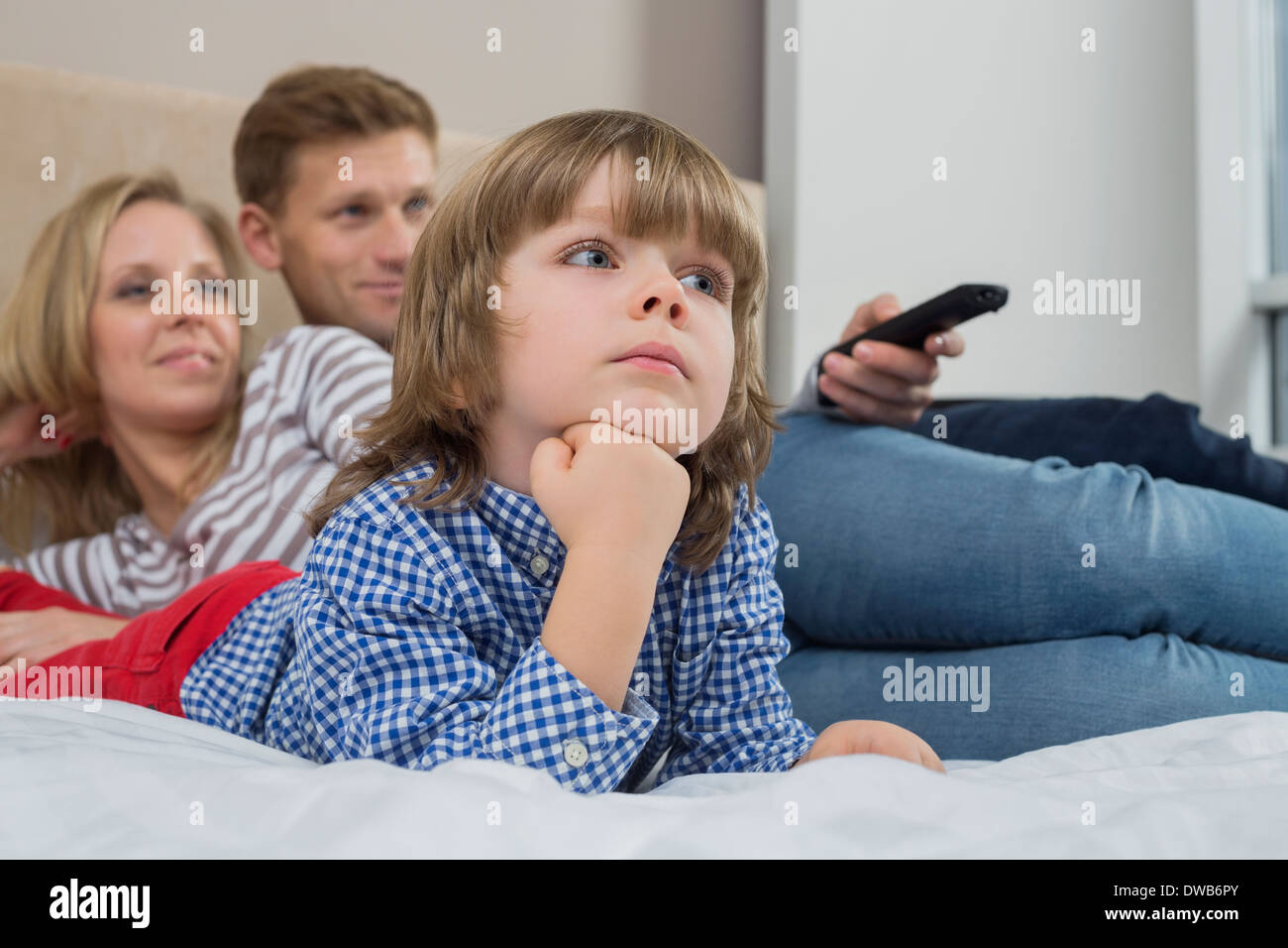 Family watching TV in bedroom - Stock Image