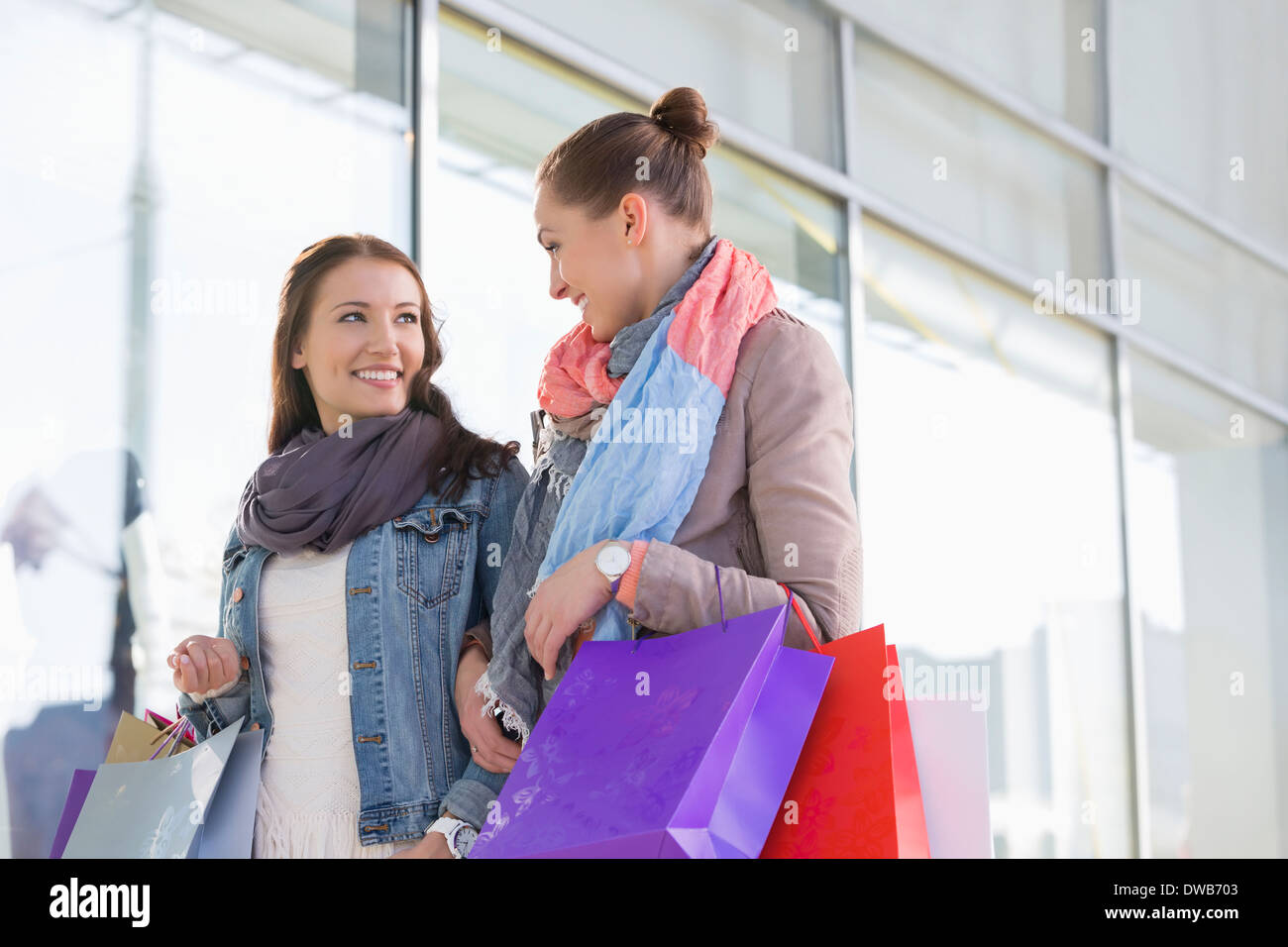Young female friends looking at each other against store - Stock Image