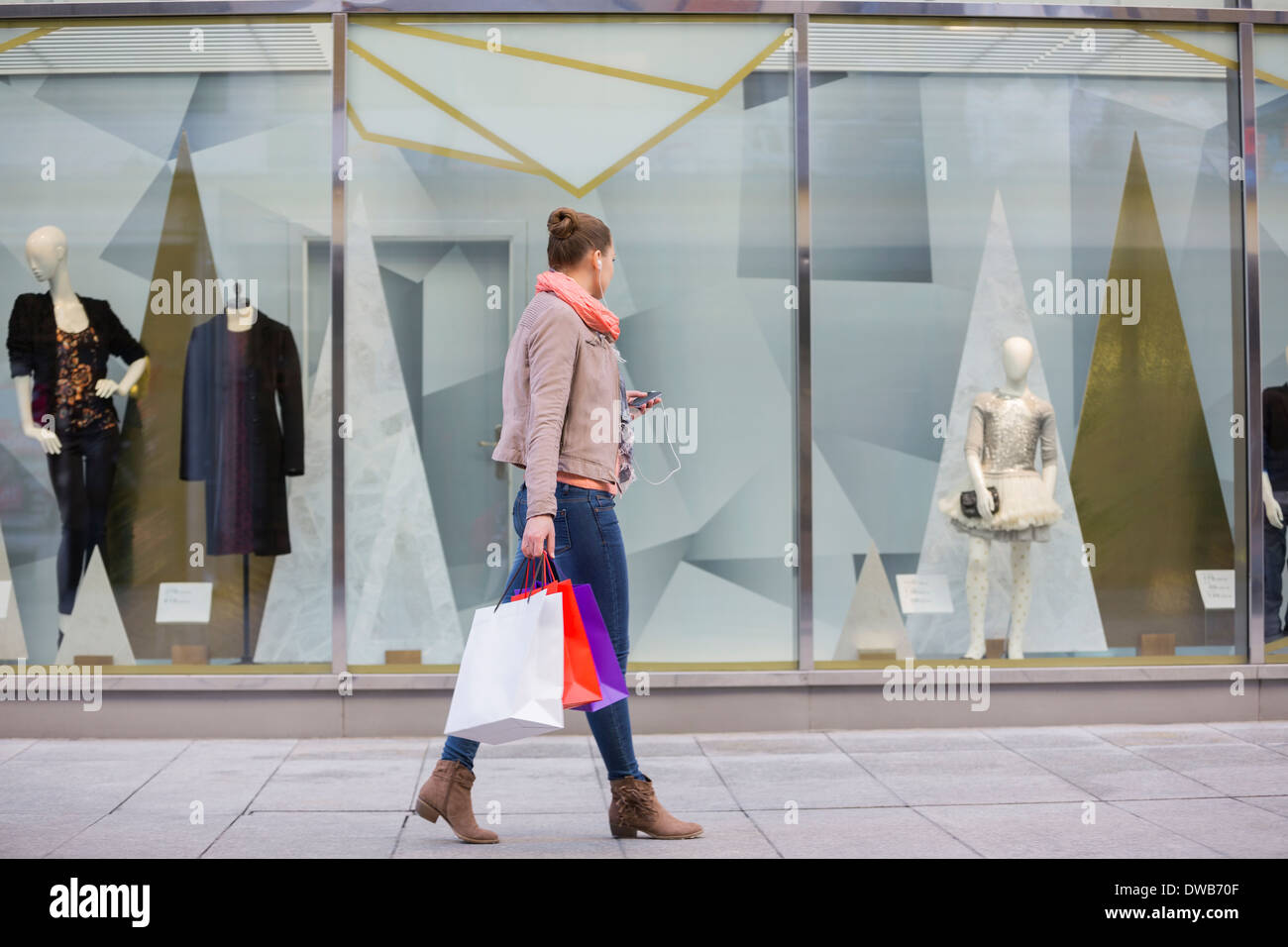 Profile shot of young woman with shopping bags looking at window display - Stock Image