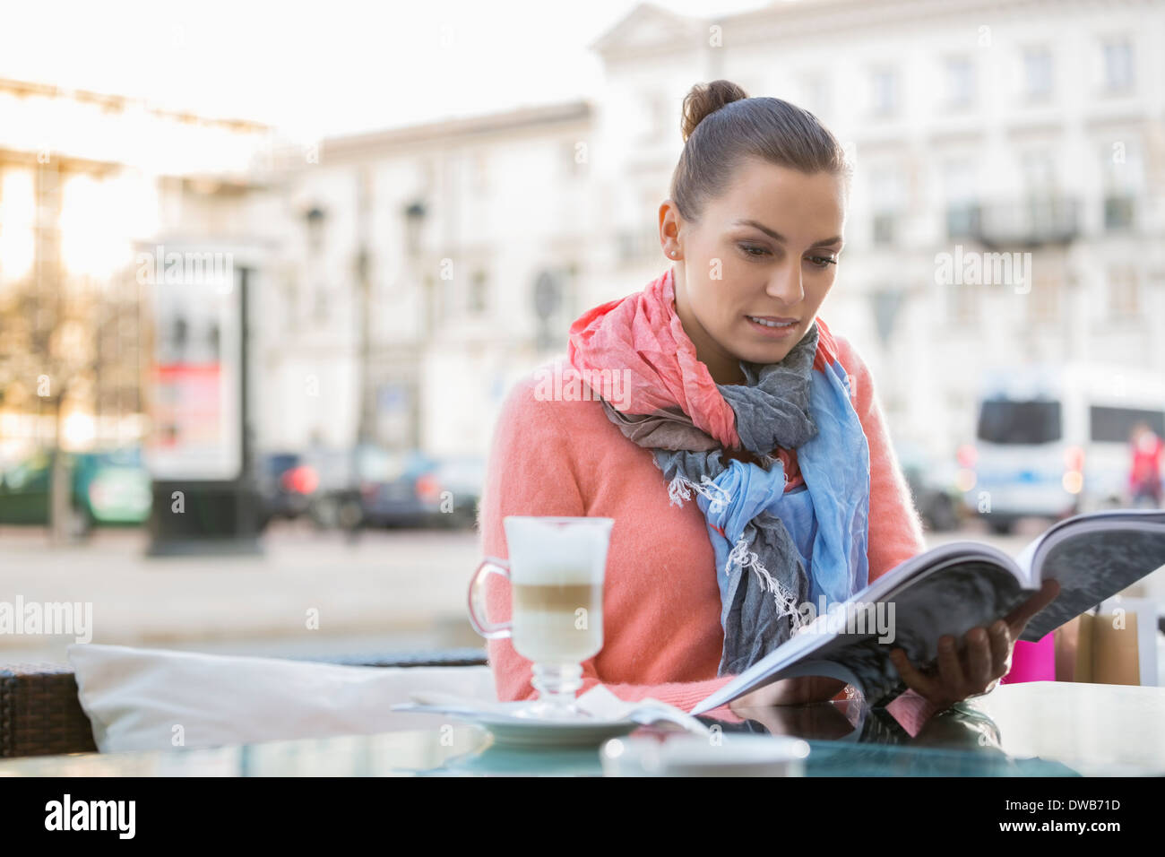 Young woman reading book at sidewalk cafe - Stock Image