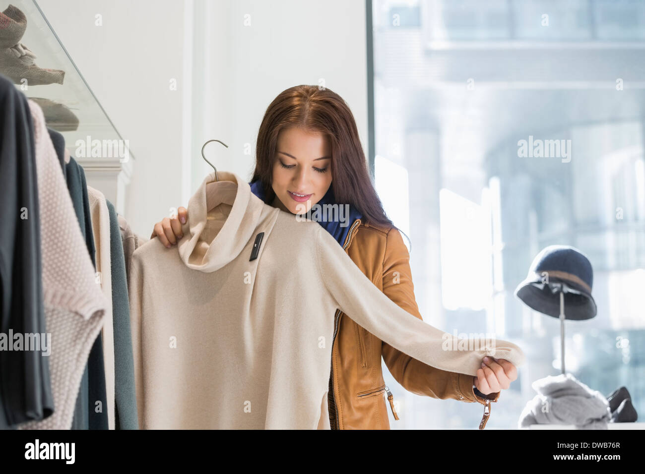 Young woman choosing sweater in store - Stock Image