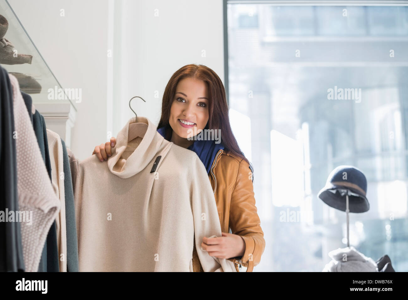 Portrait of young woman choosing sweater in store - Stock Image