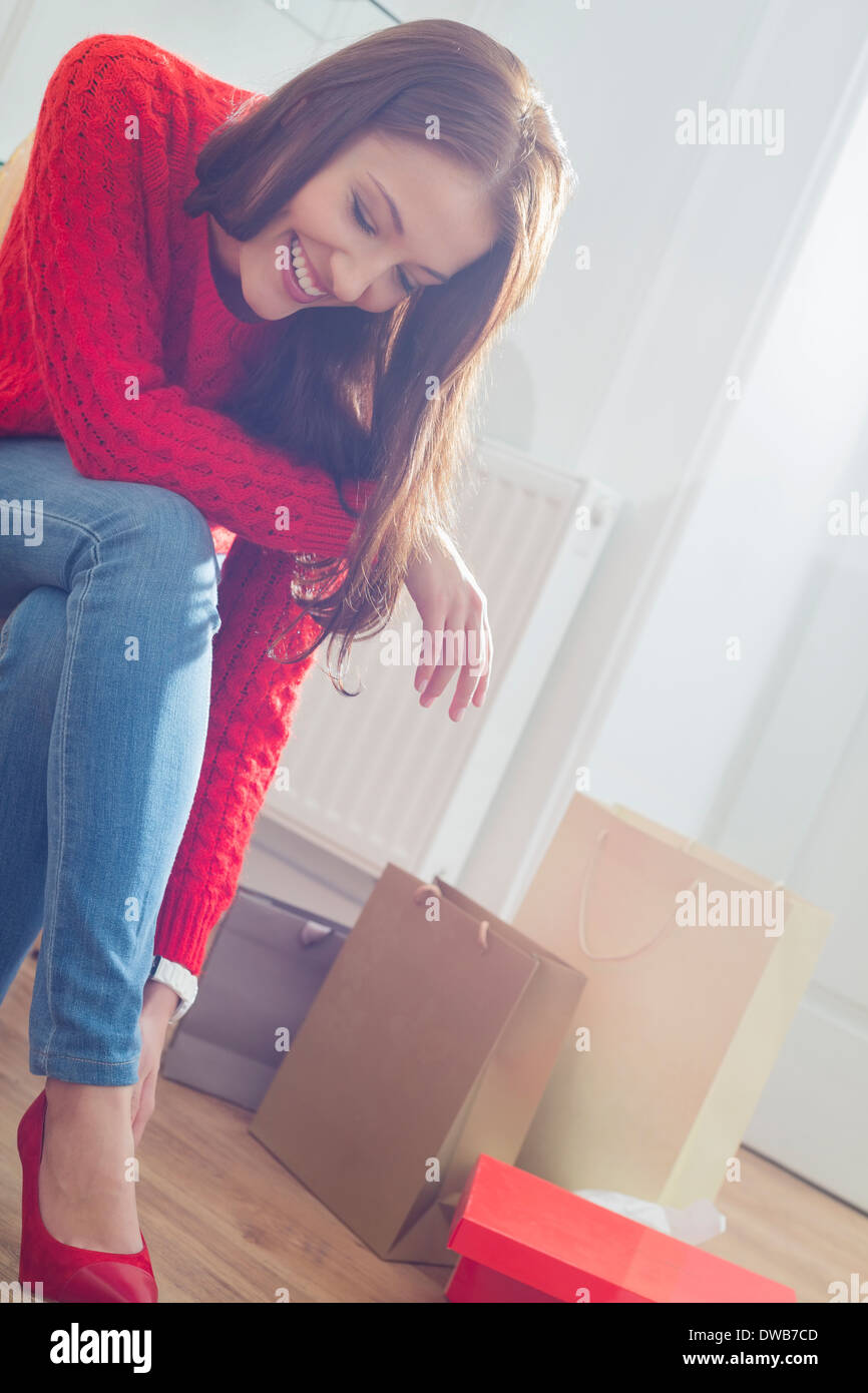 Happy young woman trying on footwear in store - Stock Image
