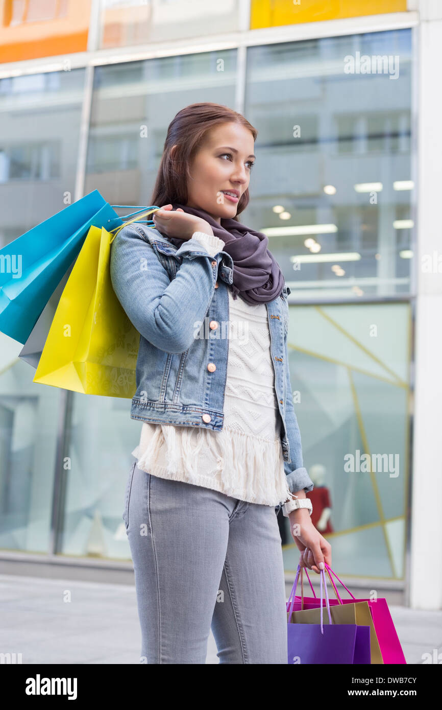 Young woman in casuals carrying shopping bags outdoors - Stock Image