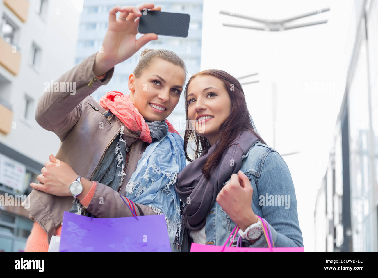 Female friends with shopping bags taking photos through mobile phone - Stock Image