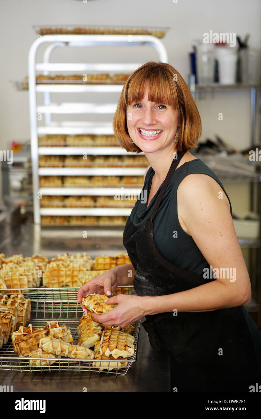 Female baker checking waffles into cooling tray - Stock Image