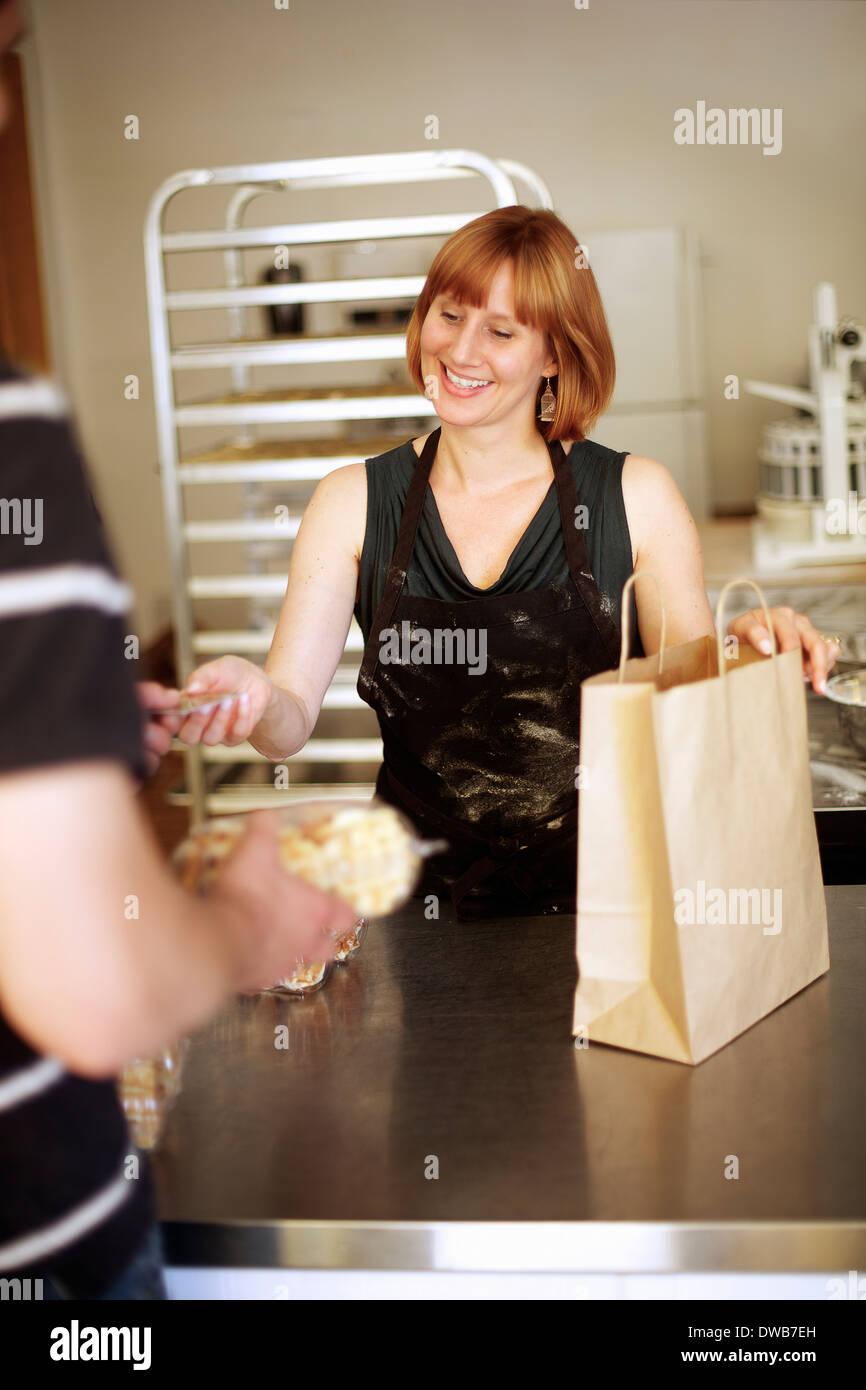 Female baker serving customer in bakery - Stock Image