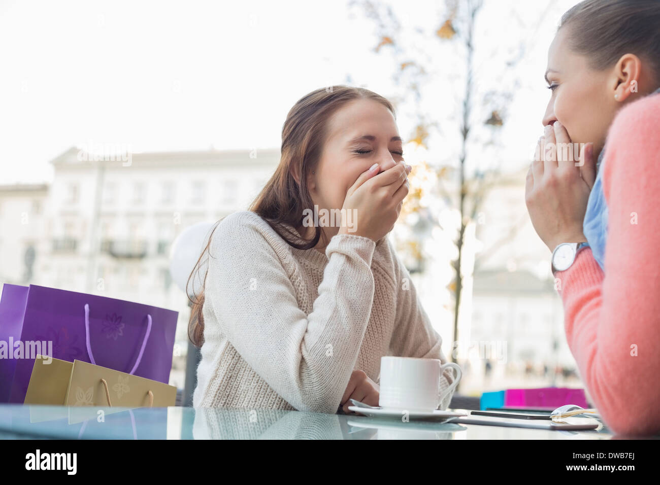 Happy women sharing secrets at outdoor cafe - Stock Image