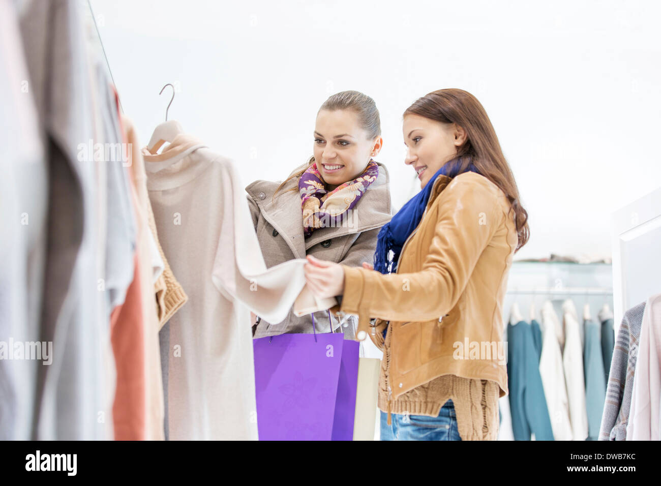 Young female friends choosing sweater in store - Stock Image