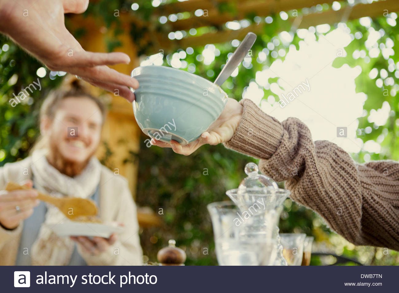 Friends passing food bowl at garden party - Stock Image