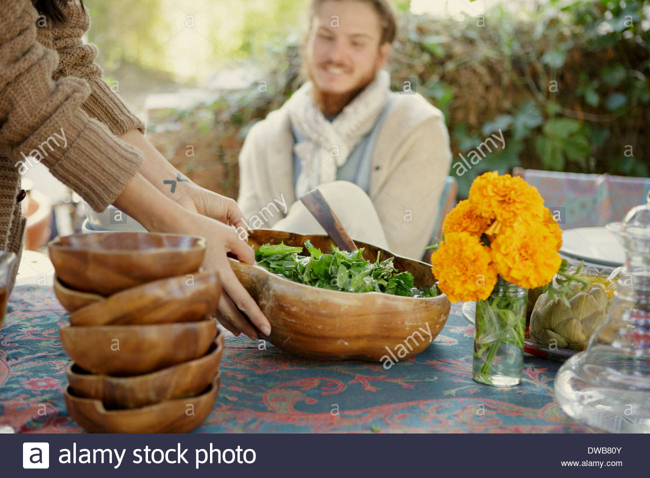 Young woman holding salad bowl at garden party - Stock Image