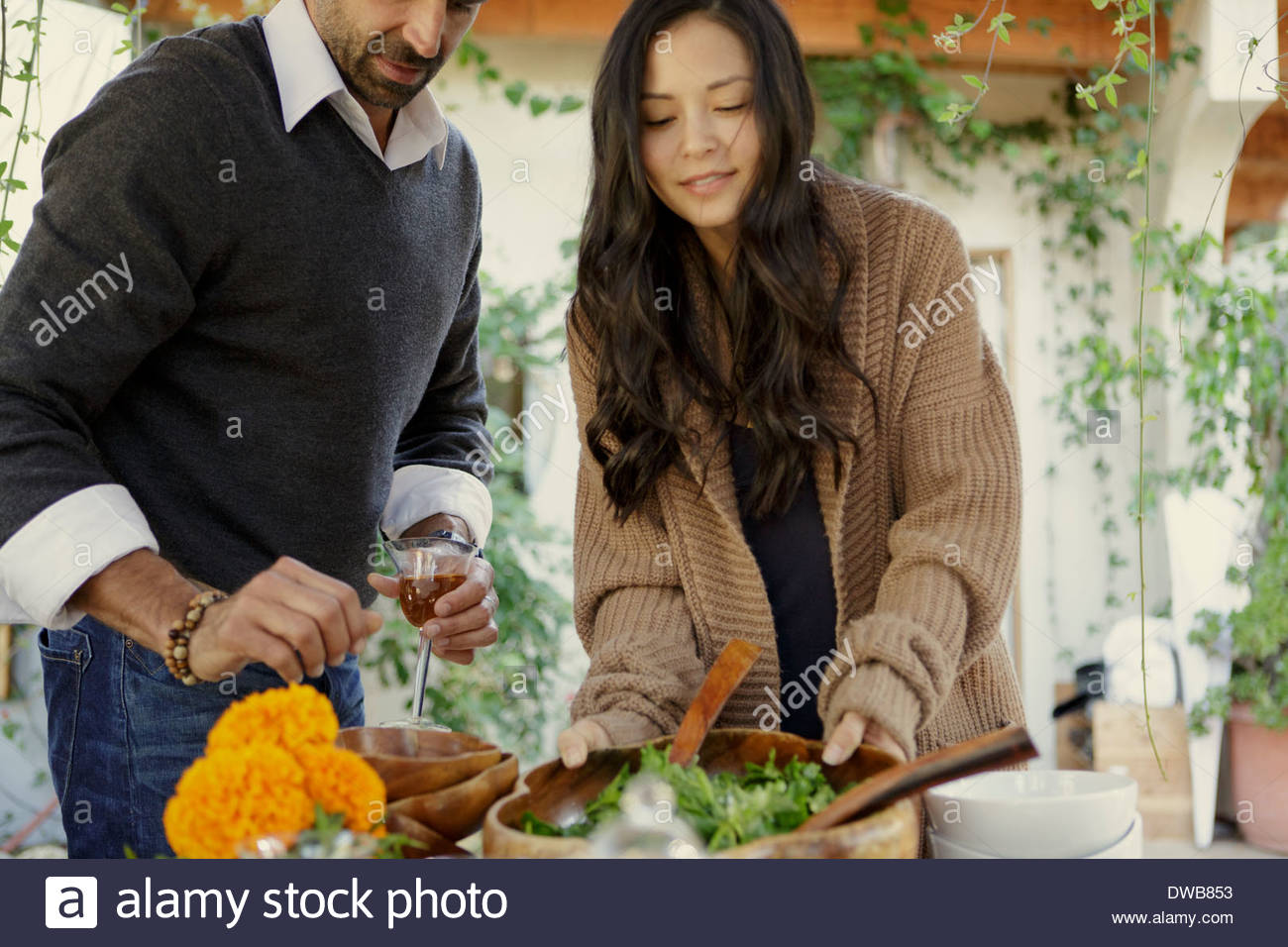 Friends selecting food at garden party - Stock Image