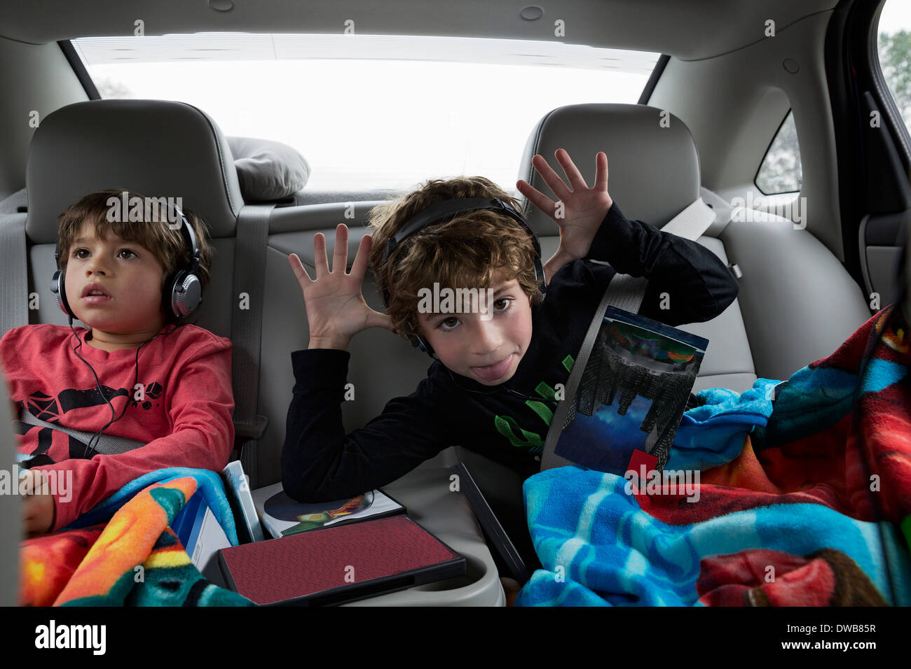 Brothers in back seat of car, wearing headphones Stock Photo