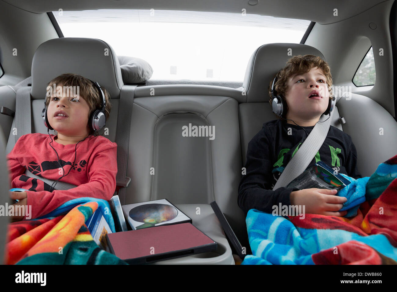 Brothers in back seat of car, wearing headphones - Stock Image