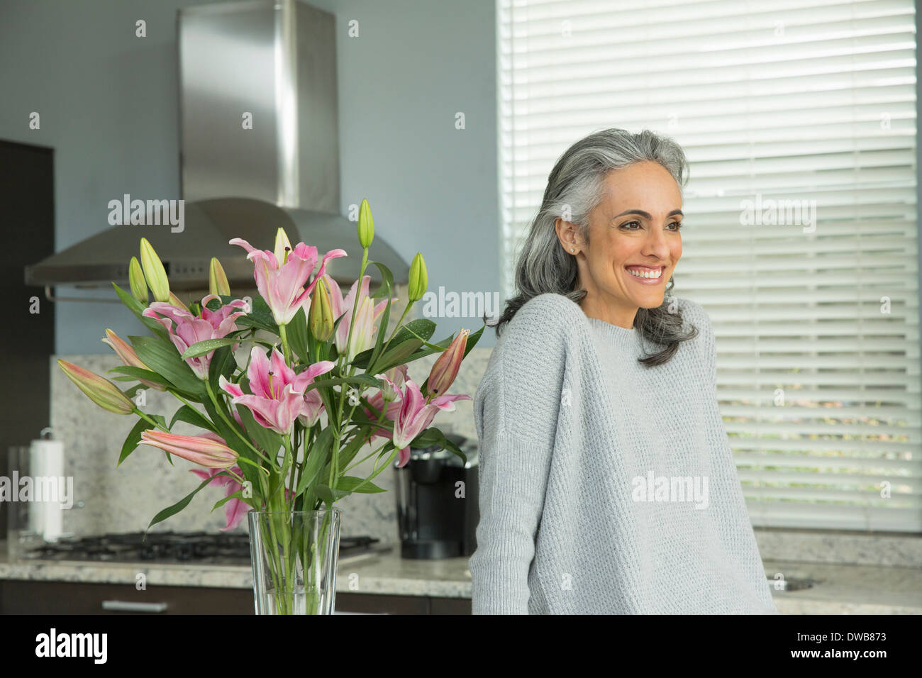 Woman by lily arrangement - Stock Image