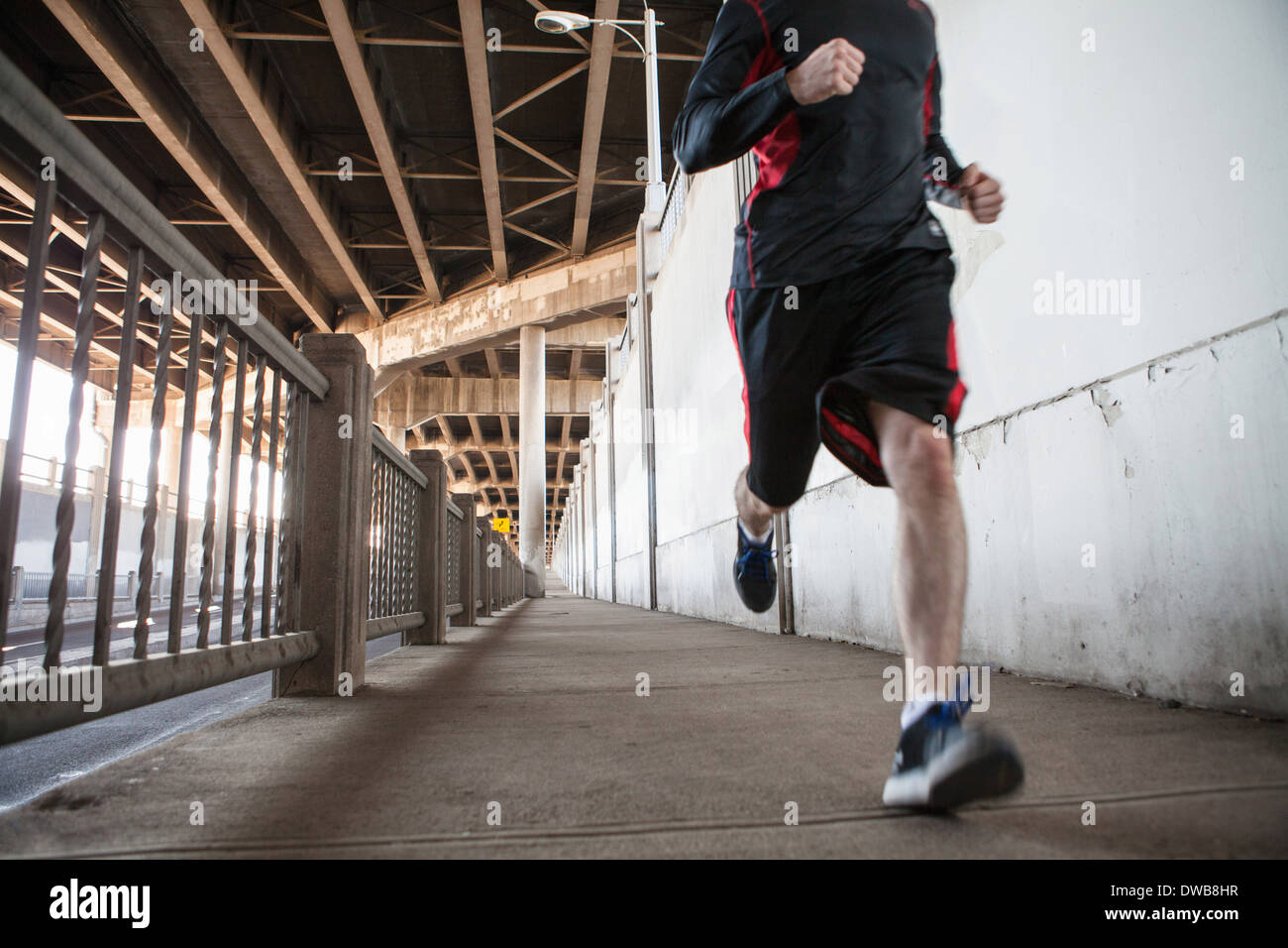 Cropped shot of young man running on city bridge - Stock Image