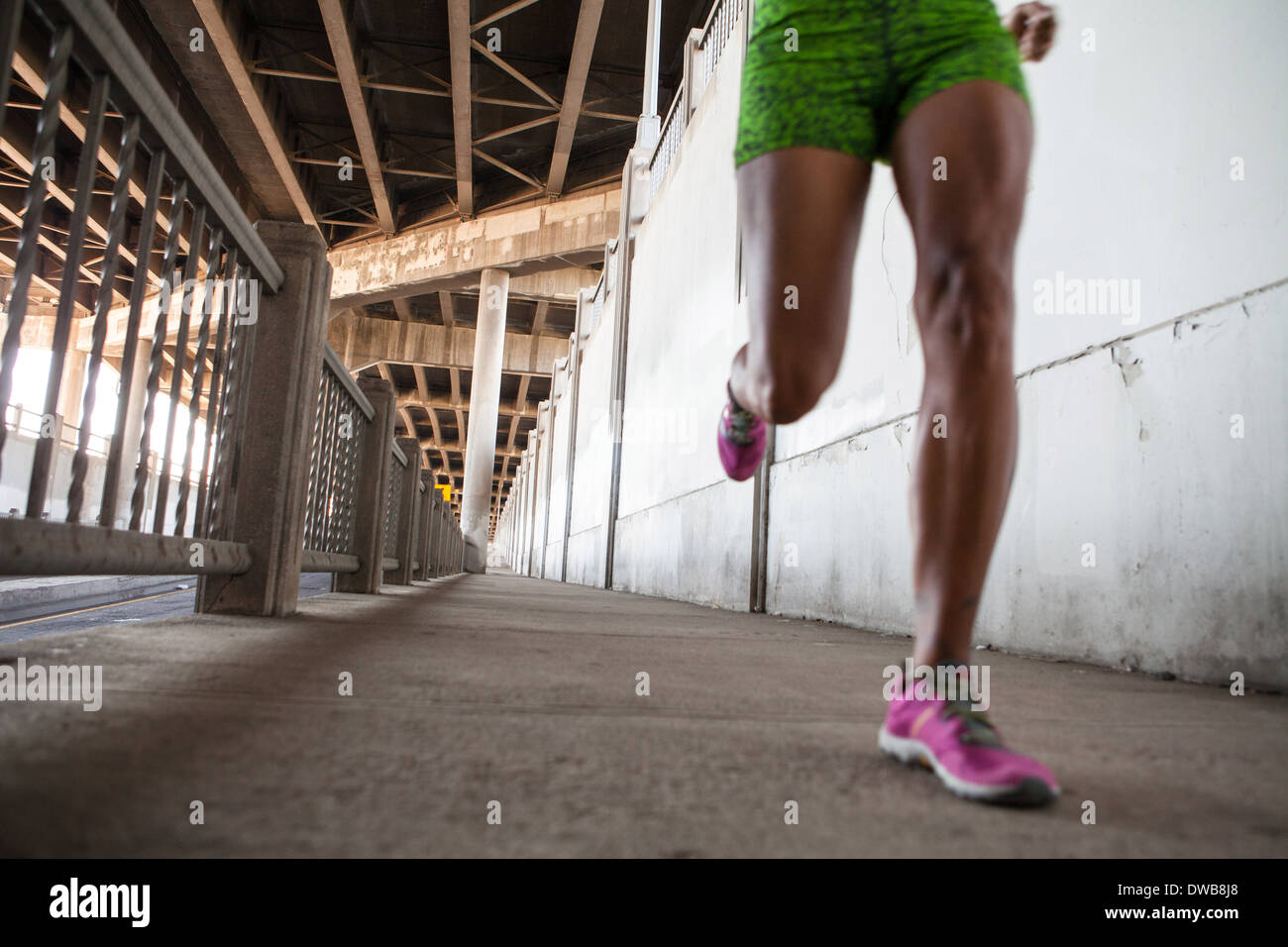 Cropped shot of young woman running on city bridge - Stock Image
