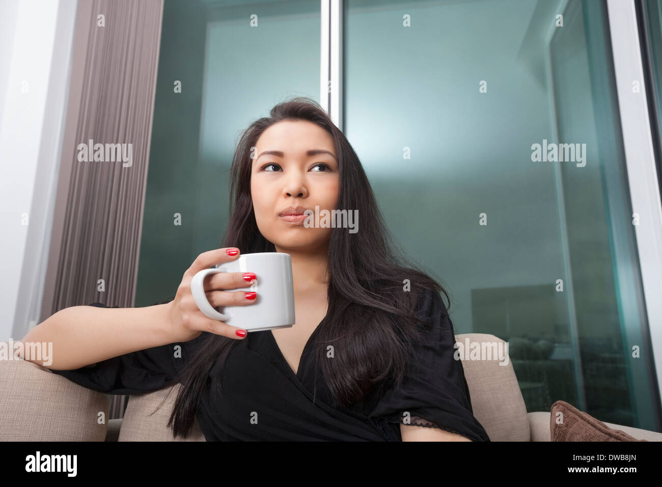 Thoughtful young woman having coffee in living room - Stock Image