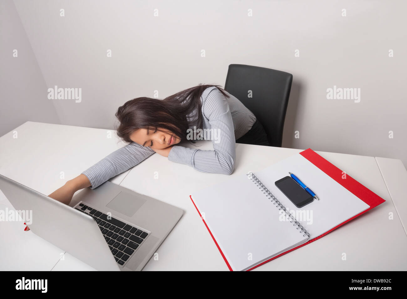 Exhausted businesswoman sleeping at office desk - Stock Image