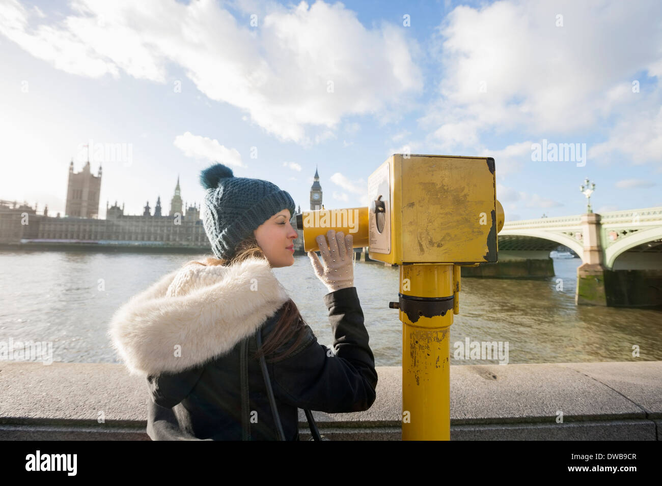 Side view of young woman looking through telescope by river Thames, London, UK - Stock Image
