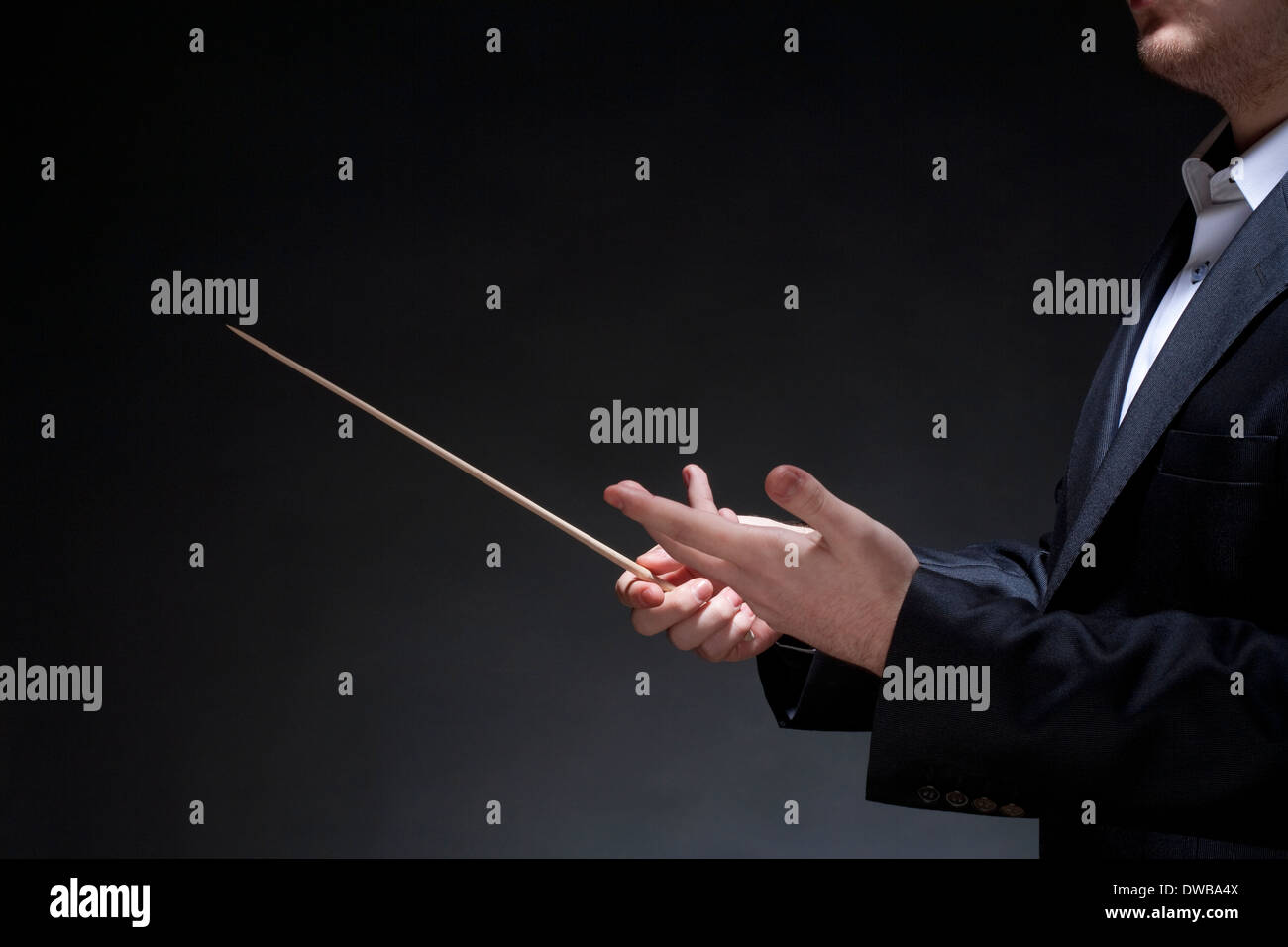 Hands of Conductor with Baton Leading Orchestra - Stock Image
