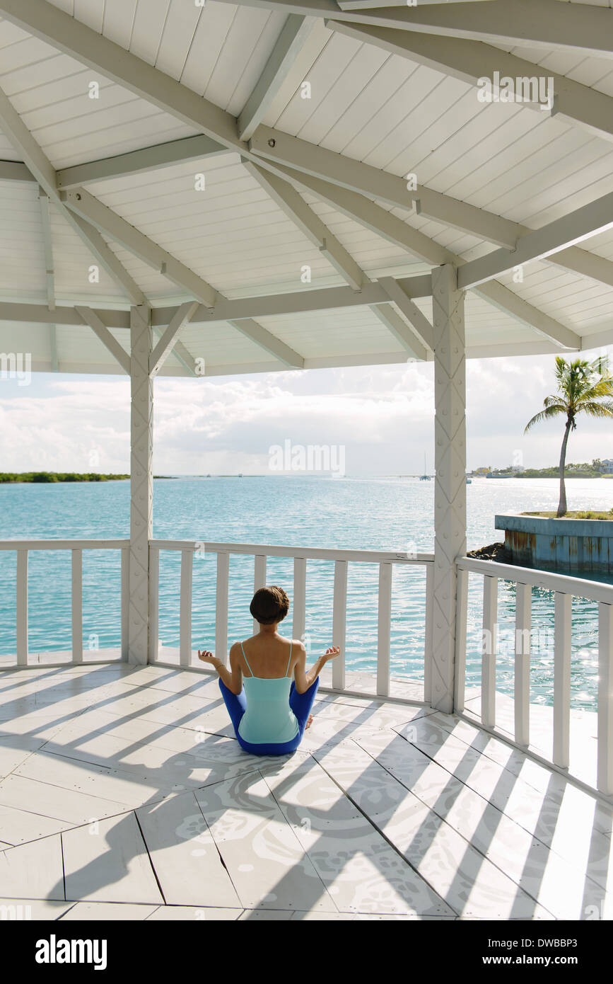 Young woman practicing yoga lotus pose in coastal gazebo, Providenciales, Turks and Caicos Islands, Caribbean - Stock Image