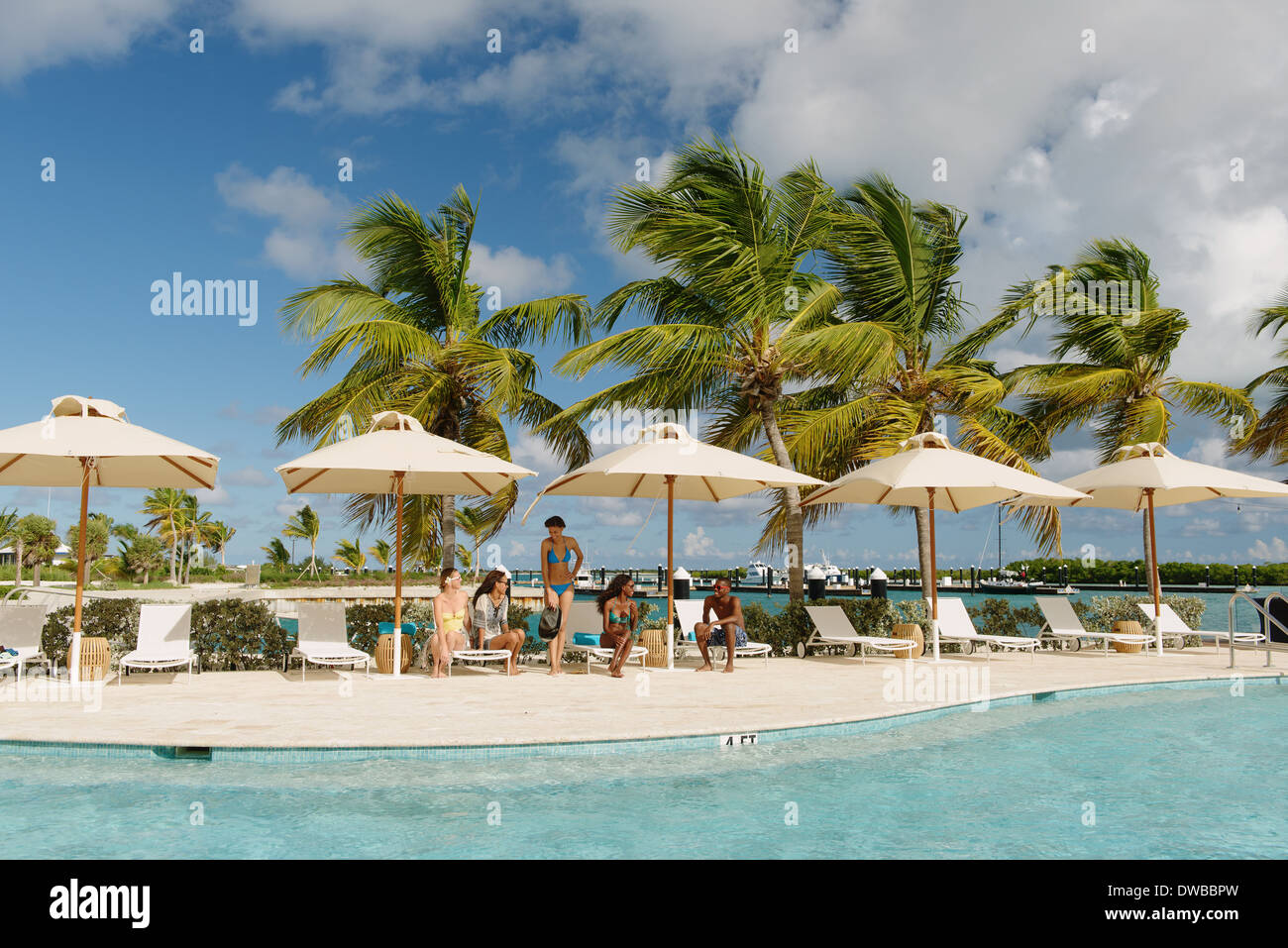 Group of young adults sunbathing by the pool, Providenciales, Turks and Caicos Islands, Caribbean Stock Photo