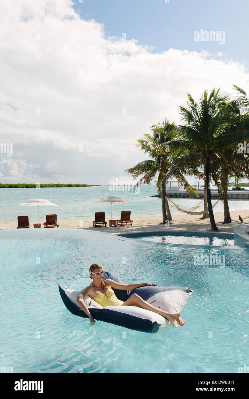 Young woman reclining on airbed in swimming pool, Providenciales, Turks and Caicos Islands, Caribbean - Stock Image