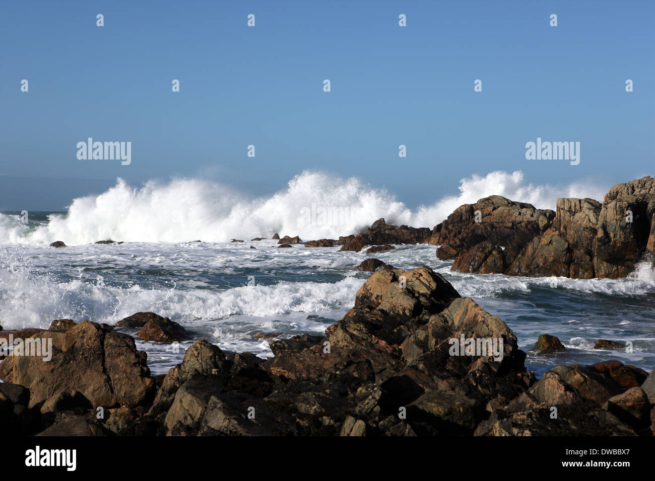 Waves crashing on the rocks on a beach in Iona one of the islands in the Inner Hebrides of Scotland - Stock Image