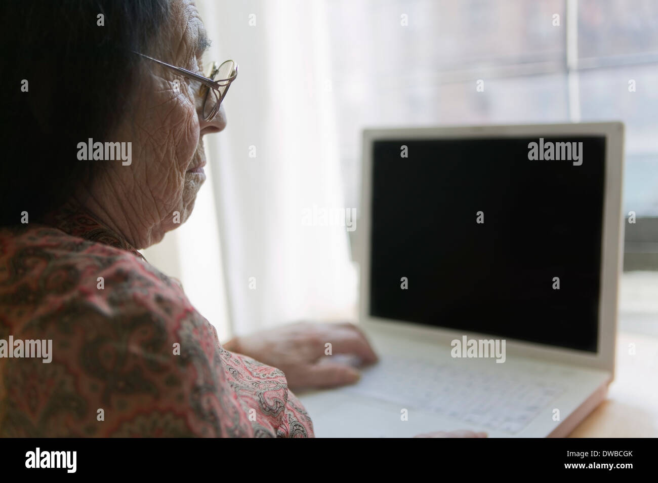 Senior woman using laptop - Stock Image