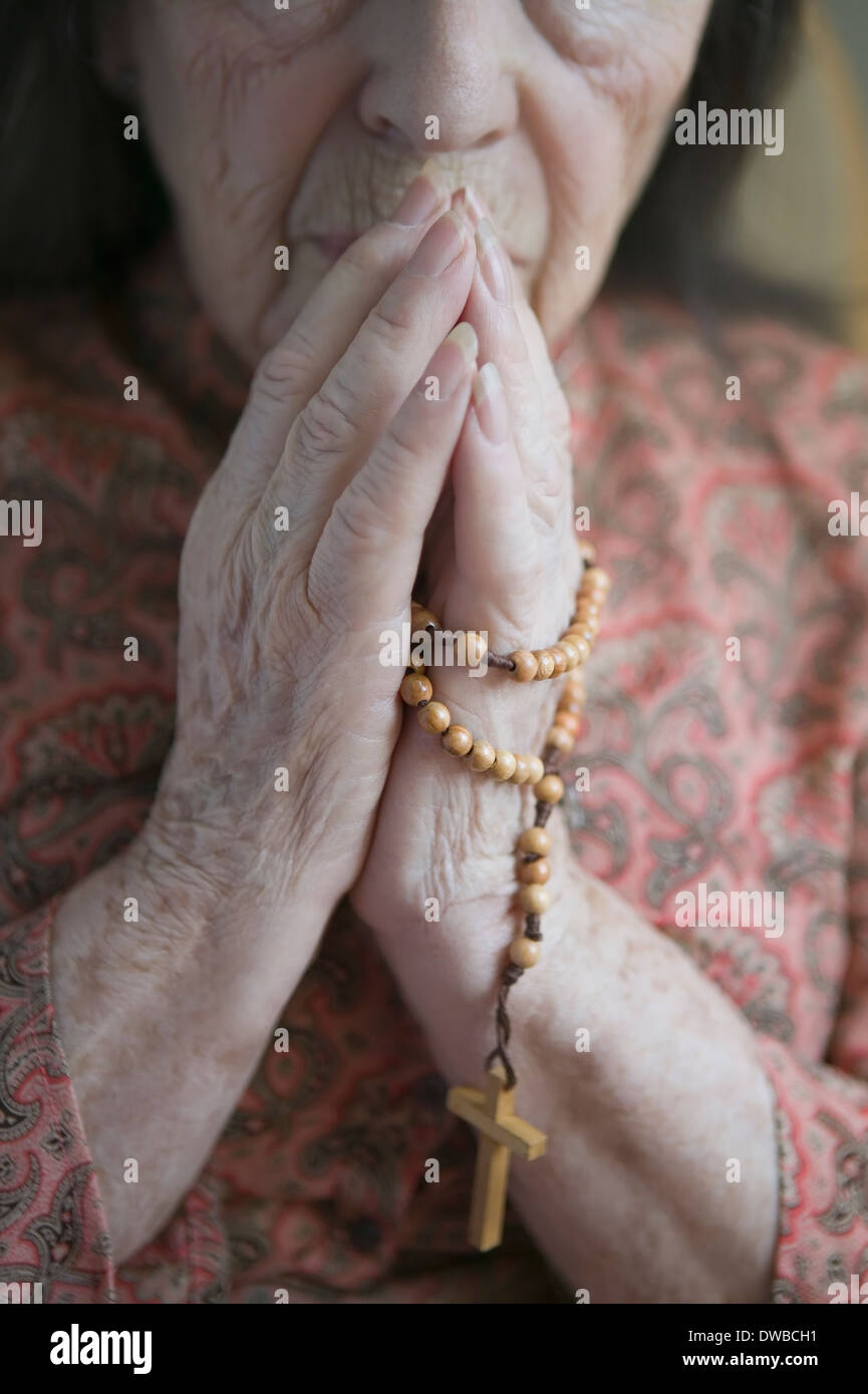 Senior woman praying with rosary - Stock Image