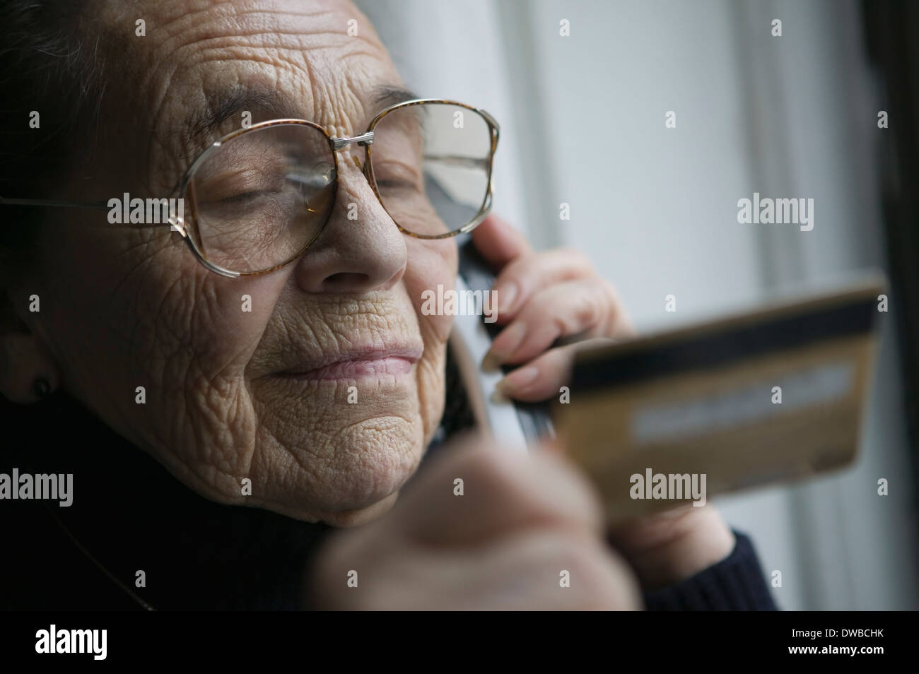 Senior woman on the phone with credit card - Stock Image