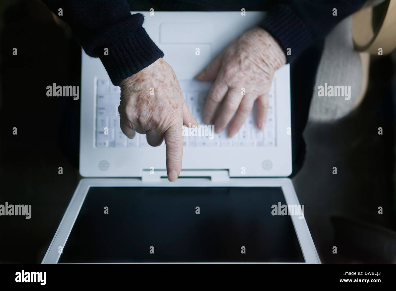 Senior woman pointing at laptop screen - Stock Image