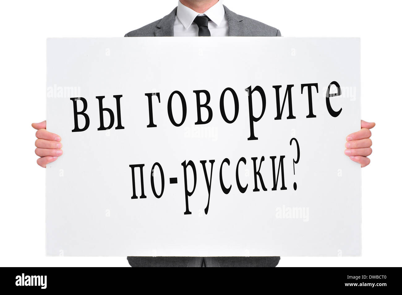 a man wearing a suit holding a signboard with the text do you speak russian? written in russian - Stock Image