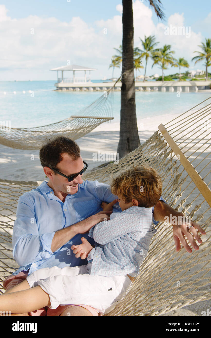 Father and son relaxing in beach hammock, Providenciales, Turks and Caicos Islands, Caribbean - Stock Image